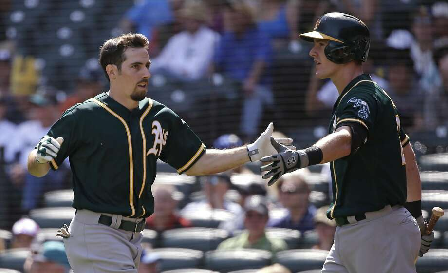 Oakland Athletics' Billy Burns, left, is congratulated on his home run by teammate Mark Canha in the first inning of a baseball game against the Seattle Mariners, Wednesday, Aug. 26, 2015, in Seattle. (AP Photo/Elaine Thompson) Photo: Elaine Thompson, Associated Press