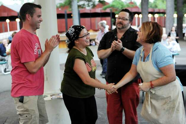 Winner Angela Crupe of Rensselaer, second from left, receives congratulations from last year's winner Jill Kavanagh of Troy, right, during the Grill Games final on Thursday, Aug. 20, 2015, at Saratoga Performing Arts Center in Saratoga Springs, N.Y. Joining them are contestants Justin Smith of Niskayuna, left, and Douglas Kinney of Clifton Park. (Cindy Schultz / Times Union) Photo: Cindy Schultz / 00033061A