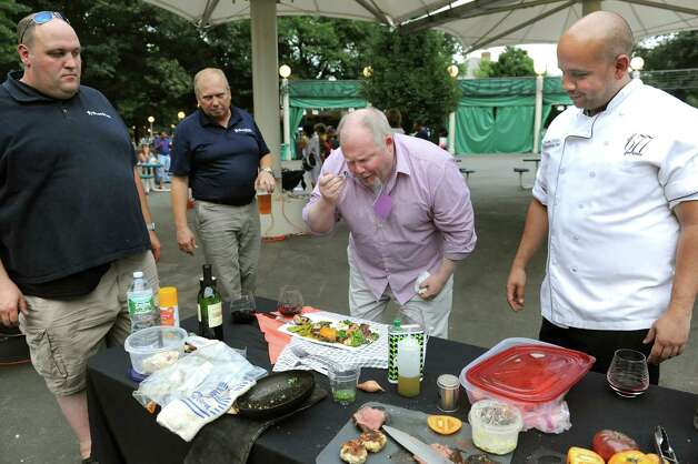 Judge Steve Barnes of the Times Union, center, samples a dish during the Grill Games final on Thursday, Aug. 20, 2015, at Saratoga Performing Arts Center in Saratoga Springs, N.Y. Joining him are fellow judges Tom Thibeault of Adirondack Appliance, left, and Jaime Ortiz of 677 Prime, right. (Cindy Schultz / Times Union) Photo: Cindy Schultz / 00033061A