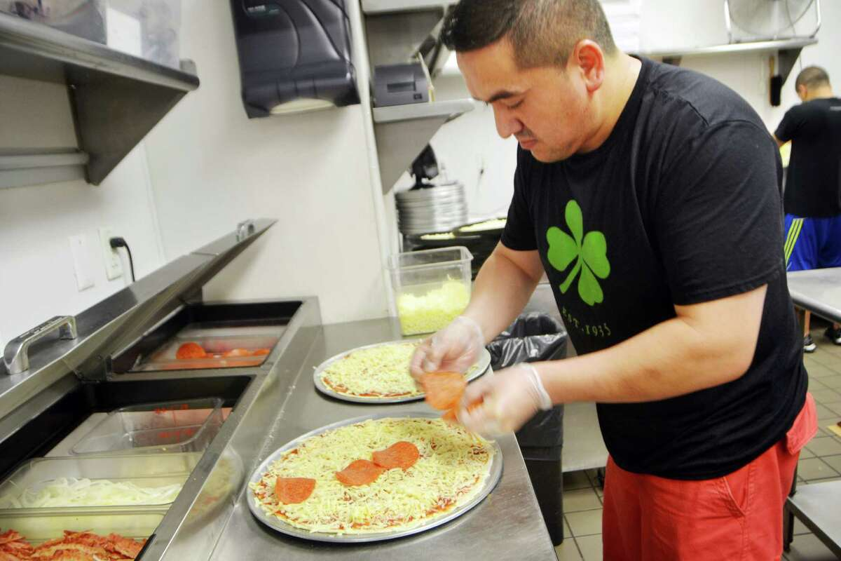 Galo Torres, kitchen manager at the Colony Grill, places pepproni on a pizza.