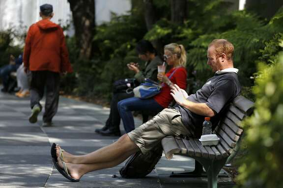 Andy Cameron of San Francisco uses his cell phone while sitting on a bench in Yerba Buena Gardens in San Francisco, California, on Wednesday, Aug. 26, 2015.