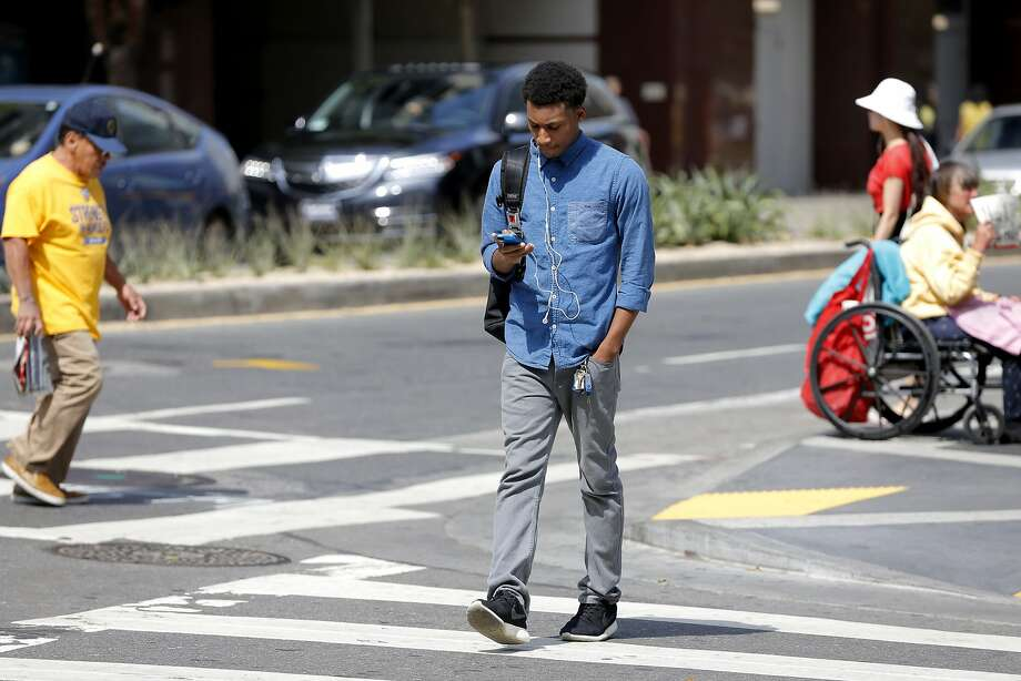 A man who did not want to be named uses his cell phone as he walks across the street in San Francisco, California, on Wednesday, Aug. 26, 2015. Photo: Connor Radnovich, The Chronicle
