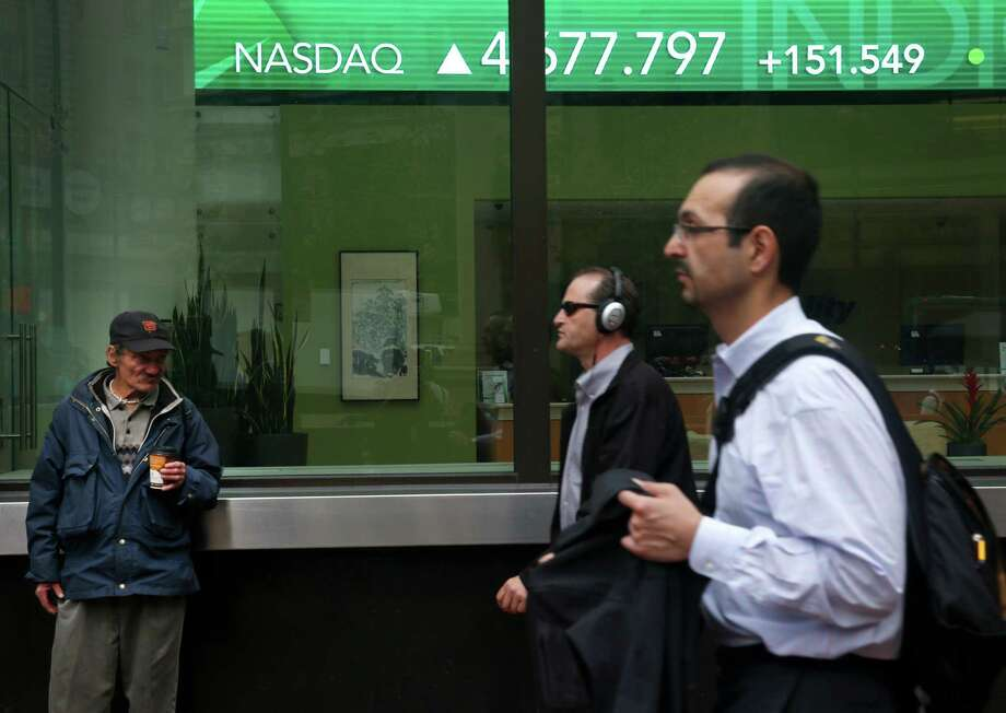 Pedestrians walk past an electronic message board on Montgomery Street in San Francisco, Calif. on Tuesday, Aug. 25, 2015 which indicates a rebound in stock market trading following Monday's deep slide. Photo: Paul Chinn / The Chronicle / ONLINE_YES