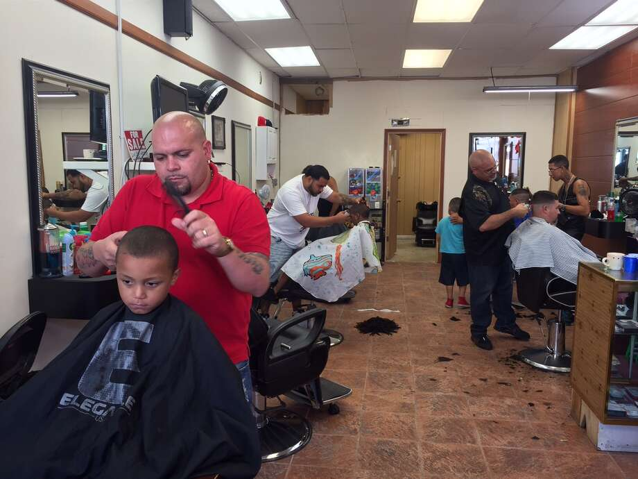 "Roberto ""Tito"" Rodriguez, top left, gives a free back-to-school haircut Wednesday at his East Side, Bridgeport, barbershop. Photo: Fausto Giovanny Pinto /Hearst Connecticut Media"
