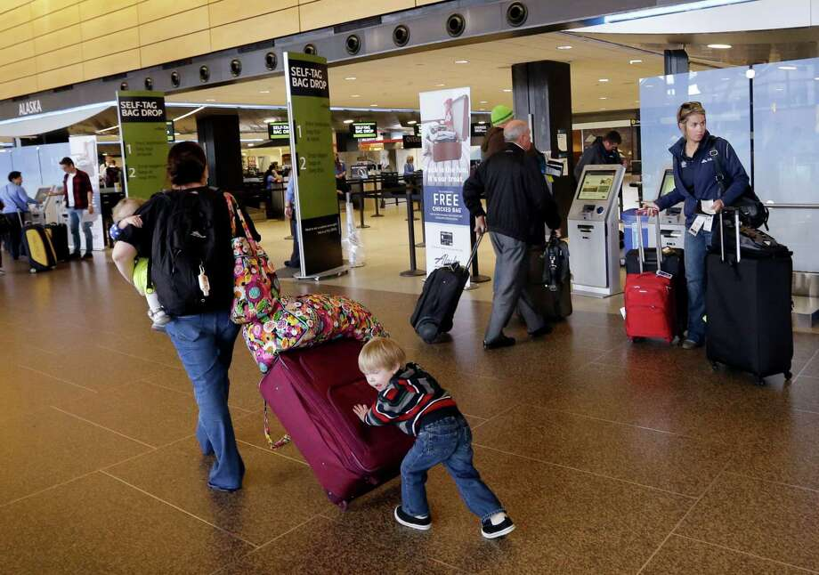 In this March 24, 2015, photo, Colin Drummond, 4, pushes luggage from behind as he walks with family members to check-in a relative for an Alaska Airlines flight at Seattle-Tacoma International Airport in SeaTac, Wash. Fliers in certain markets are seeing bargain flights as fare wars make a limited return. (AP Photo/Elaine Thompson) ORG XMIT: NYBZ213 Photo: Elaine Thompson / AP