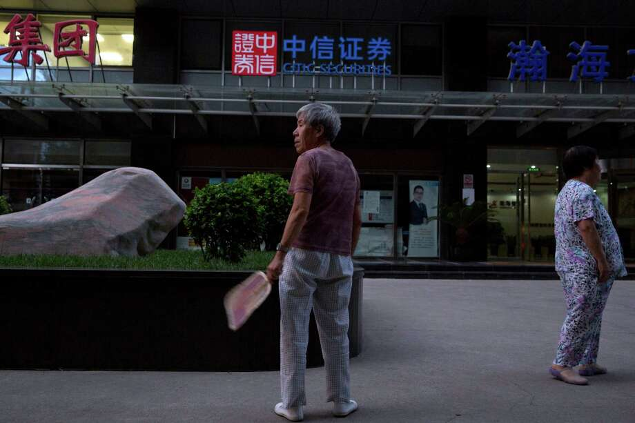 An elderly woman stands near the Citic Securities in Beijing on Wednesday, Aug. 26, 2015. Employees of state-owned Citic Securities Ltd, one of China's biggest securities firms and one current and one former employee of its market regulator are under investigation on suspicion of illegal stock trading, state media reported Wednesday, amid the collapse of a stock price boom.(AP Photo/Ng Han Guan) ORG XMIT: XHG110 Photo: Ng Han Guan / AP