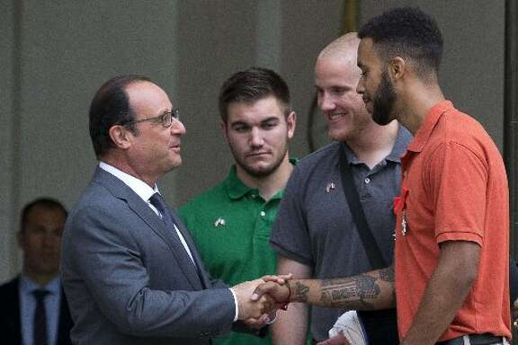 French President Hollande shakes hands with Anthony Sadler (from right), Spencer Stone, Alek Skarlatos.