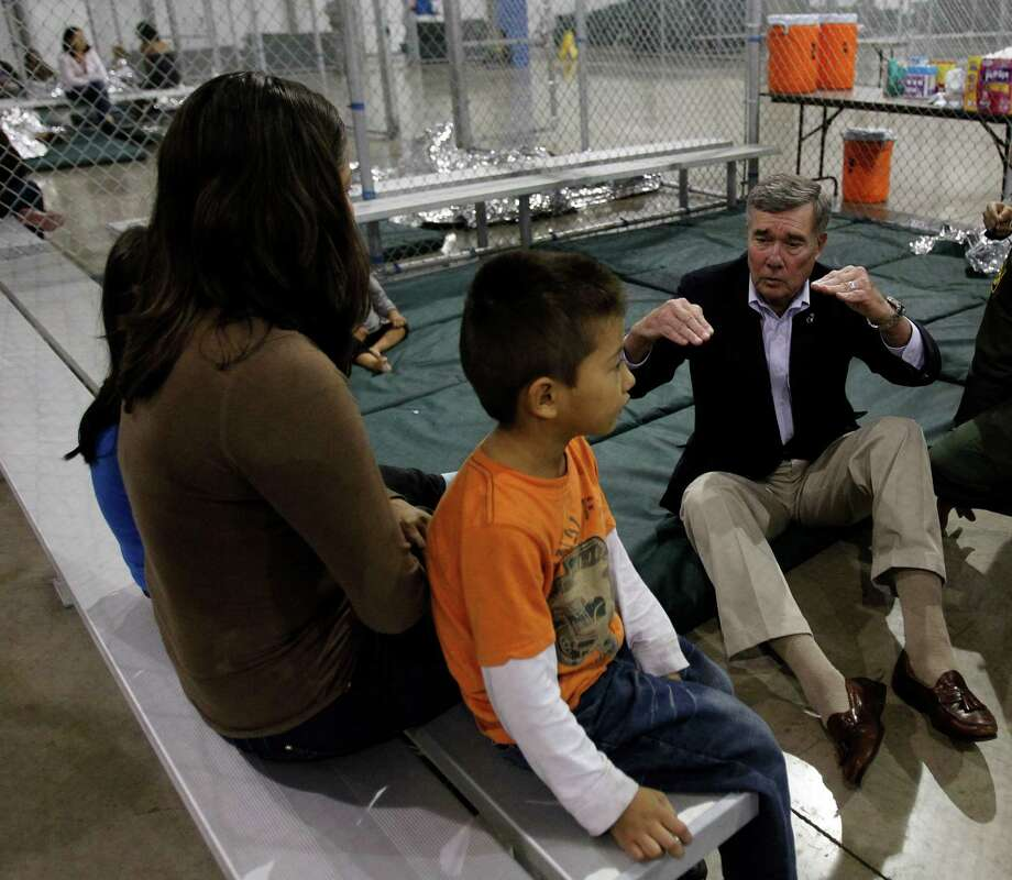 MCALLEN — Gil Kerlikowske, commissioner of U.S. Customs and Border Protection, sits on the floor to talk with a family Wednesday at a processing center in McAllen. Photo by Delcia Lopez dlopez@themonitor.com Photo: Delcia Lopez /AP / Delcia Lopez photography