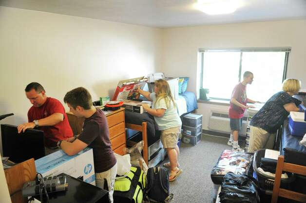 Mike Ecker, left, of Colonie and his wife JoEllen Ecker, third from left, help their son, Brendan set up his room as Christopher Insinna, fourth from left, from Staten Island and his mom, Joan Insinna unpack his belongings as first year students at the Albany College of Pharmacy and Health Sciences moved into their rooms on Wednesday, Aug. 26, 2015 in Albany, N.Y.  All other students will move in on Thursday.  (Paul Buckowski / Times Union) Photo: PAUL BUCKOWSKI / 00033111A