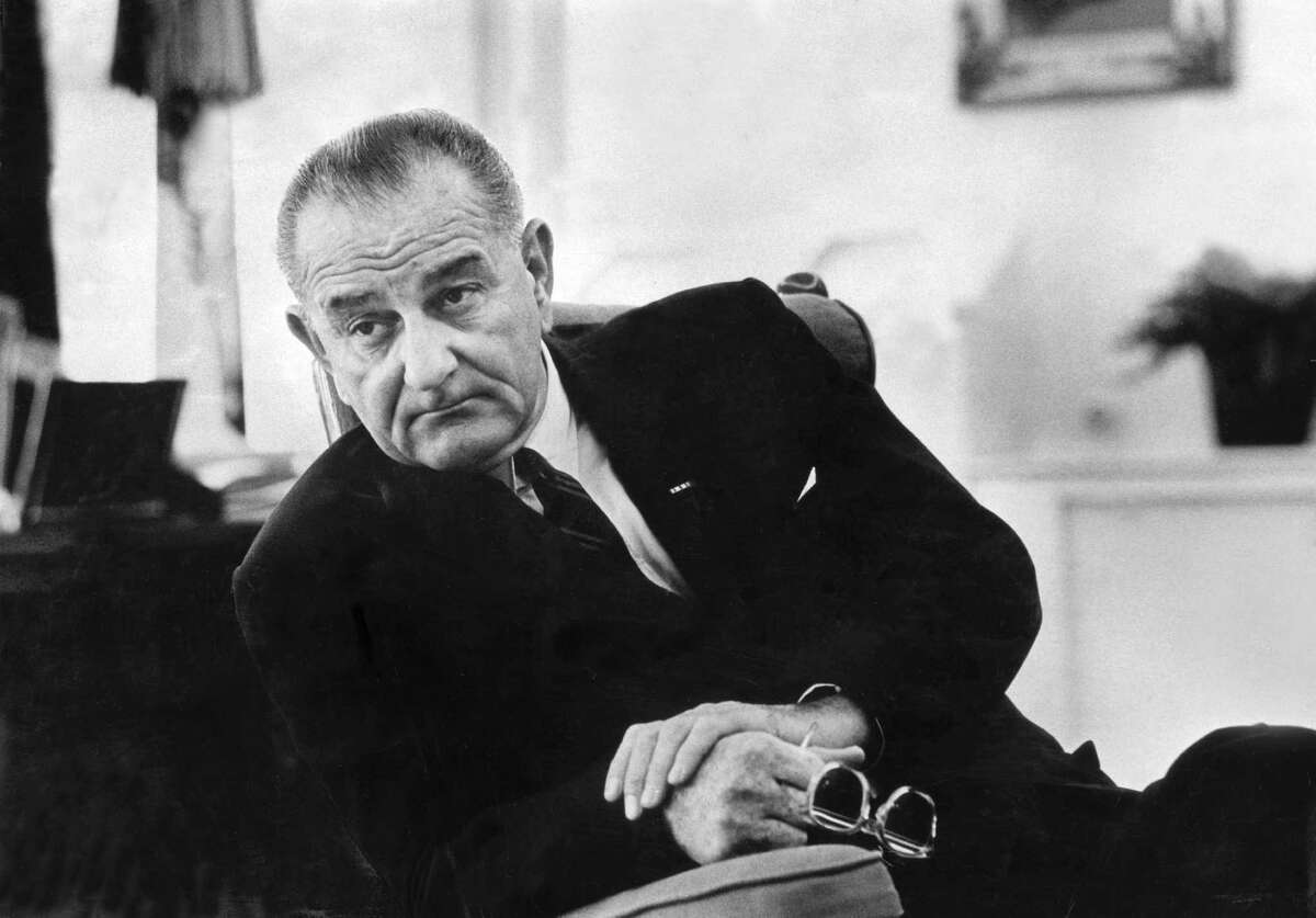 This 1966 file photo shows President Lyndon B. Johnson in the Oval Office of the White House in Washington. His legislative milestones in helping others are being chipped away by conservative policymakers.