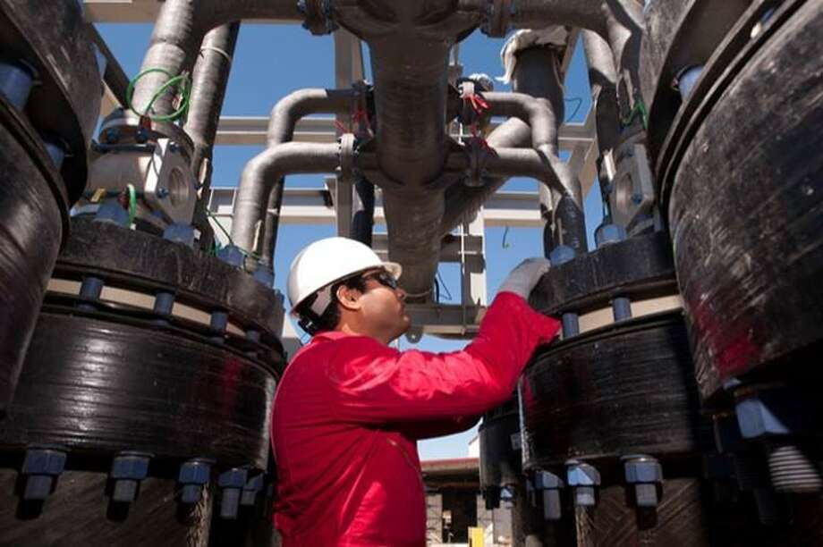 In an undated photo from a 2015 investor presentation, a Cameron International worker examines oil field separation and processing equipment produced by the Houston-based manufacturer. Schlumberger said on Aug. 26, 2015, that it would acquire Cameron in a $12.8 billion deal. (Cameron International photo) Photo: Cameron International