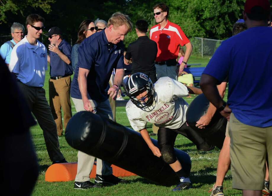 NFL Commissioner Roger Goodell assists some of the young Fairfield Giants football players with their skills during practice at Sullivan Field in Fairfield, Conn., on Wednesday Aug. 4, 2015. Goodell was on hand to talk to parents, coaches and the kids and to see the progress made on the Heads Up program. The program promotes better and safer tackling in football. Photo: Christian Abraham / Hearst Connecticut Media / Connecticut Post