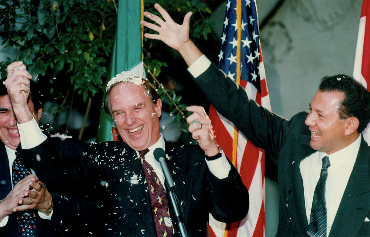 In a Nov. 18, 1993, Express-News file photo, Mayor Nelson Wolff and Mexican General Humberto Haddad break cascarones on each other at the Spanish Governor's Palace to celebrate Congress approving NAFTA.