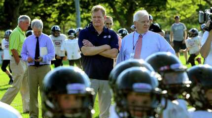 NFL Commissioner Roger Goodell, arms crossed, watches as some o