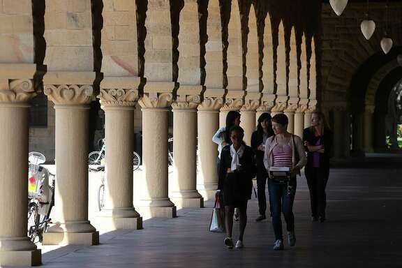 STANFORD, CA - MAY 22:  People walk through the Stanford University campus on May 22, 2014 in Stanford, California. According to the Academic Ranking of World Universities by China's Shanghai Jiao Tong University, Stanford University ranked second behind Harvard University as the top universities in the world. UC Berkeley ranked third.