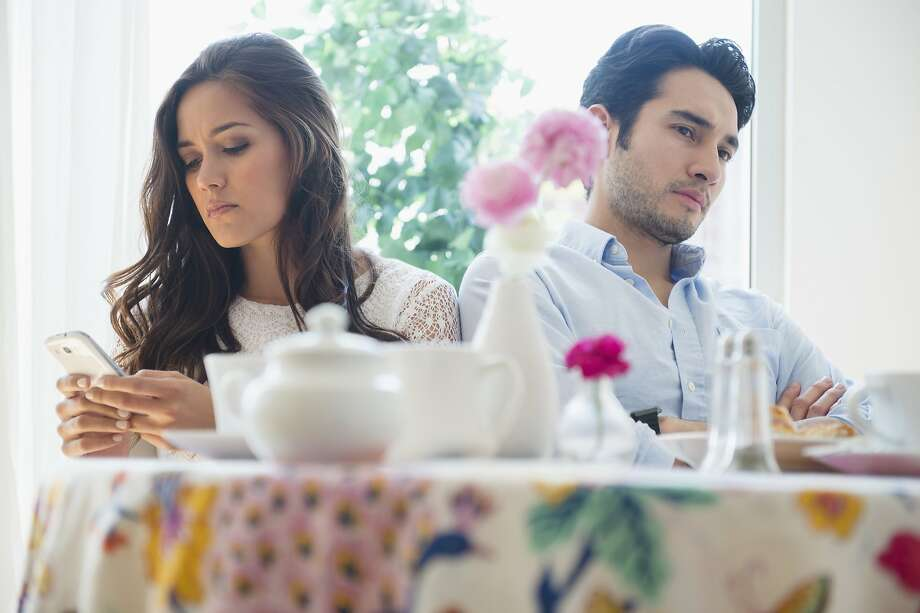 A husband is upset that his wife seems more interested in her phone than him. Photo: JGI/Jamie Grill