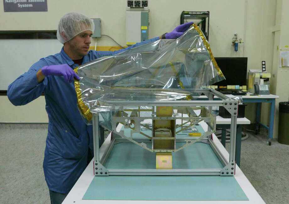 Nicholas Alexander covers the frame of the first of eight satellites of CYGNSS, a system of eight separate satellites to measure from space surface wind speed in hurricanes. The satellites are being developed and assembled at the Southwest Research Institute in San Antonio. Photo: Billy Calzada, Staff / San Antonio Express-News / San Antonio Express-News
