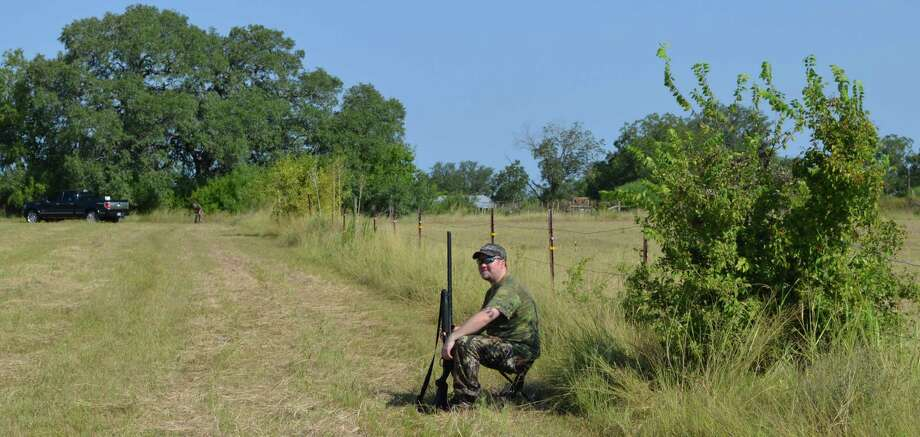 Zane Goodspeed tries to find a little shade along a fence line in eastern Bexar County during last year's opening day before he tested his shooting skills on mourning and white-winged doves along with members of the Sportsman Club of San Antonio. Photo: Ralph Winingham /For The Express-News