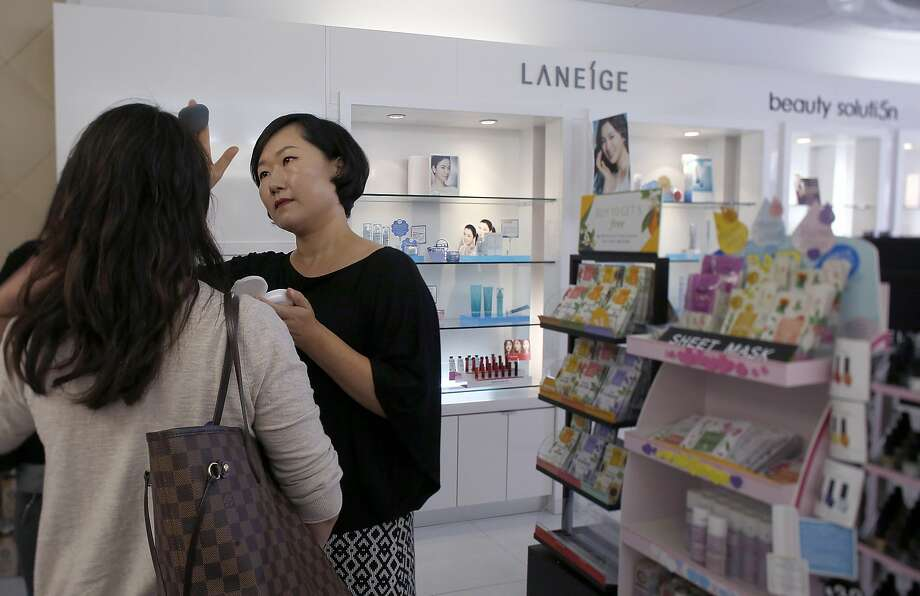 Amore sales associate Sarah Jung applies make up to a customer in Santa Clara, Calif., on Thursday, August 20, 2015. Photo: Liz Hafalia, The Chronicle