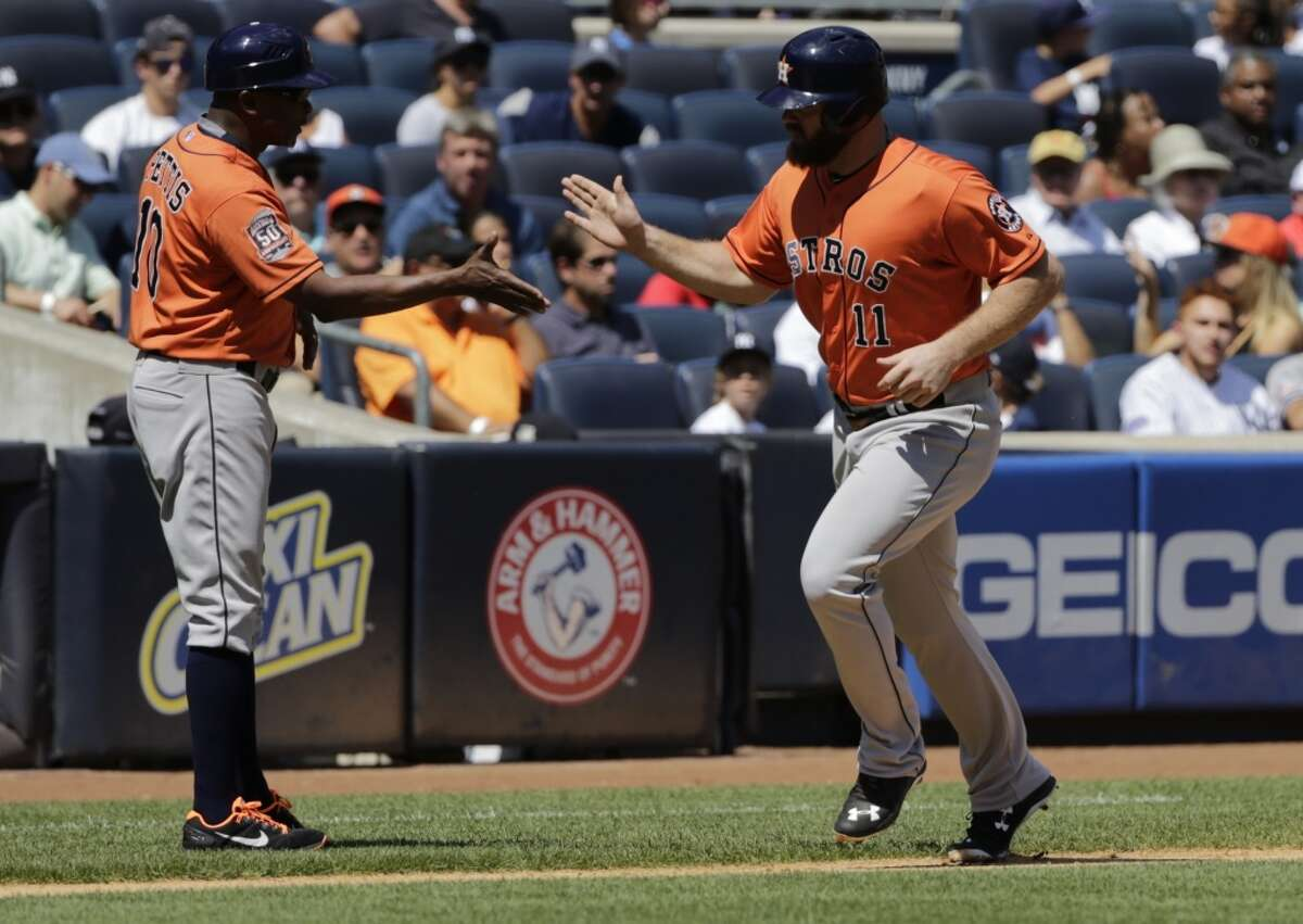 Houston Astros' Evan Gattis celebrates with third base coach Gary Pettis on his way to home plate after hitting a home run during the second inning of a baseball game Wednesday, Aug. 26, 2015, in New York. (AP Photo/Frank Franklin II)