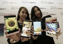 FILE - In this Sept. 24, 2014 file photo, Models pose with Samsung Electronics Co.'s latest Galaxy Note 4 and Galaxy Note Edge smartphones as they are unveiled in Seoul, South Korea.  By the end of the year, there are expected to be about 7 billion cell phone subscriptions _ about the same as the world's population. (AP Photo/Ahn Young-joon, File)