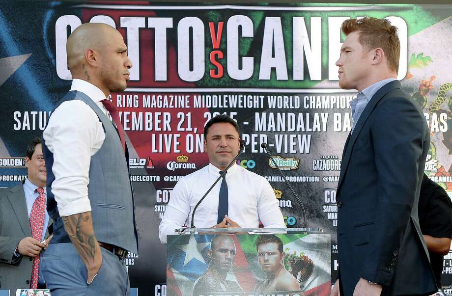 Oscar De La Hoya (center), Chairman and CEO, Golden Boy Promotions, looks on as current WBC champion Miguel Cotto (left) and contender Canelo Alvarez, former WBC and WBA super welterweight world champion, pose during a news conference to announce their upcoming WBC middleweight title bout Aug. 24, 2015, in Los Angeles. The WBC middleweight title bout will take place Nov. 21 at the Mandalay Bay Events Center in Las Vegas, Nevada. Photo: Kevork Djansezian /Getty Images / 2015 Getty Images