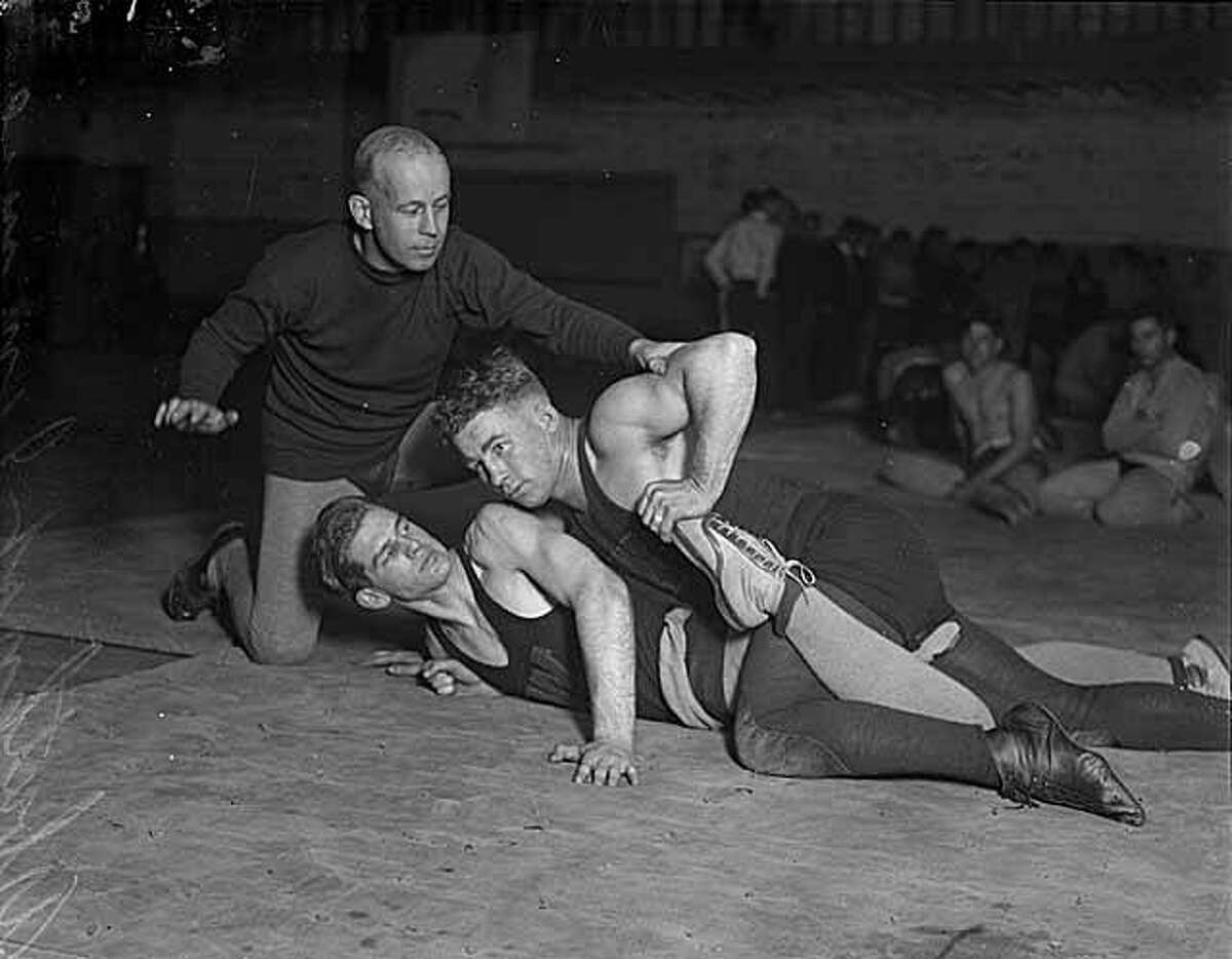 University of Washington wrestling coach James Arbuthnot pictured with two wrestlers in what appears to be a posed portrait. Photo dated 1925.