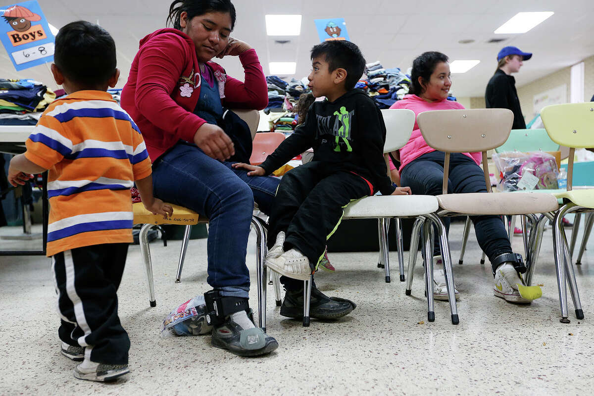 Guatemalan immigrant Maria Romelia Marin Chaclan, 27, wears an ankle monitor as she and her sons wait for intake at the Sacred Heart Catholic Church shelter, Thursday, May 21, 2015. According to volunteers, they started noticing adult immigrants with the monitors, provided by U.S. Customs and Immigration Enforcement, on May 13. After they are processed by immigration, some of the immigrants are released on their own recognizance with a date to appear before an immigration judge at the arrival destination in the US. The monitors are used to insure that they show up before a judge according to an immigration statement.