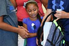 Greenwich rising first-grader Anna Lily Cruz takes a backpack filled with school supplies at Town Hall in Greenwich, Conn. Thursday, Aug. 27, 2015.  For the seventh year, the Greenwich Rotary Club and Department of Social Services provided backpacks and back-to-school supplies for children free of charge.