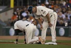 San Francisco Giants' Matt Duffy, left, is checked on by first base coach Bill Hayes against the Chicago Cubs during the first inning of a baseball game in San Francisco, Wednesday, Aug. 26, 2015. (AP Photo/Jeff Chiu)