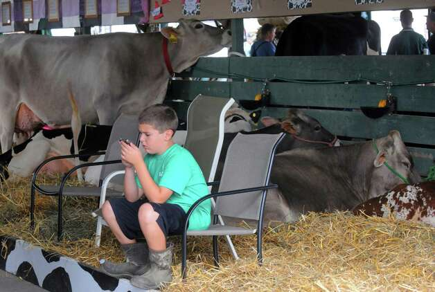 Ten-year-old Clay Bates of Argyle plays a video game while cow-sitting during the Washington County Fair on Thursday Aug. 27, 2015 in Greenwich, N.Y. The Washington County Fair runs through Sunday. (Michael P. Farrell/Times Union) Photo: Michael P. Farrell / 10032909A