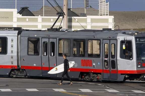 A surfer walks past an N-Judah streetcar at La Playa Street before it makes a return trip inbound in San Francisco, Calif. on Thursday, Aug. 27, 2015. Muni is getting ready to roll out a second round of major service improvements systemwide.