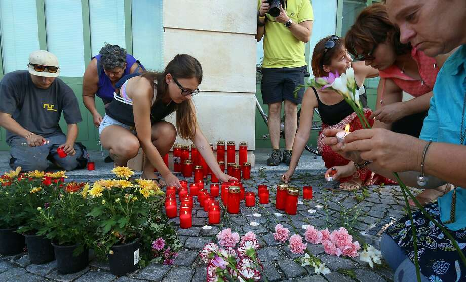 People light candles at a memorial in Eisenstadt, Austria, to honor the dead migrants. Photo: Ronald Zak, Associated Press