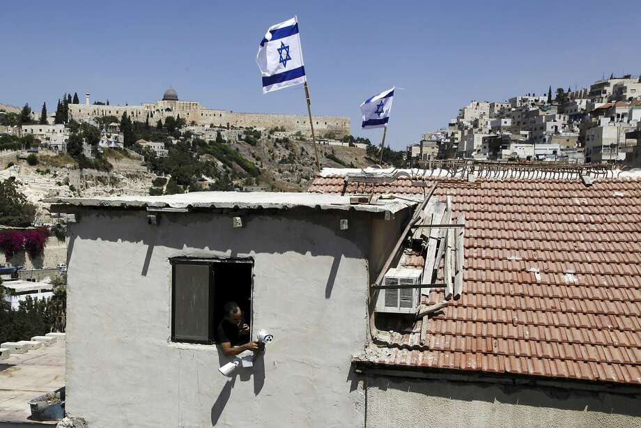Israeli flags fly on top of a house in the Silwan neighborhood of East Jerusalem. Photo: Mahmoud Illean, Associated Press