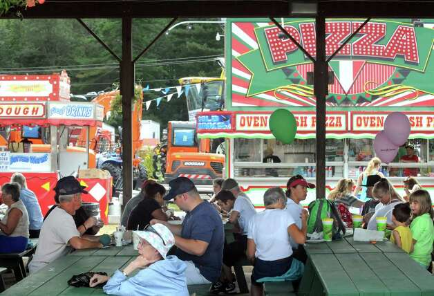 Fairgoers relax from the heat in the shade of a pavilion and partake in the many fair foods available during the Washington County Fair on Thursday Aug. 27, 2015 in Greenwich, N.Y. The fair runs through Sunday. (Michael P. Farrell/Times Union) Photo: Michael P. Farrell / 10032909A