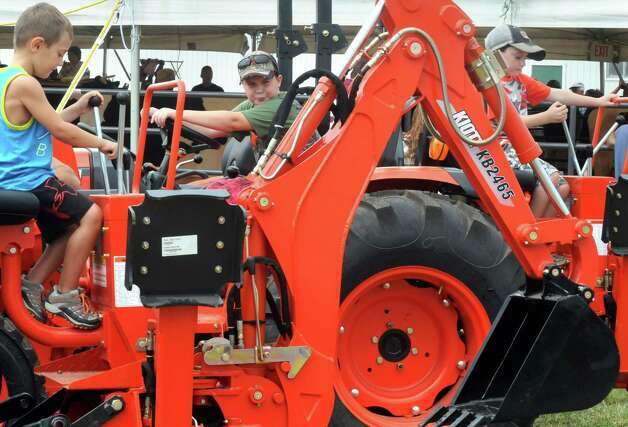 Five-year-old Lucas Raybne, left, of Fort Ann joins other boys trying out tractors during the Washington County Fair on Thursday Aug. 27, 2015 in Greenwich, N.Y. The Washington County Fair runs through Sunday. (Michael P. Farrell/Times Union) Photo: Michael P. Farrell / 10032909A