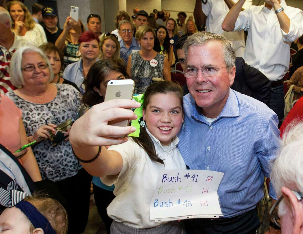 Eden Blackman, 13, of Mobile, Ala., left, takes a photo of herself with Jeb Bush, the Republican presidential candidate and former Florida governor, after he spoke at the Pensacola Bay Center in Pensacola, Fla., on Wednesday.