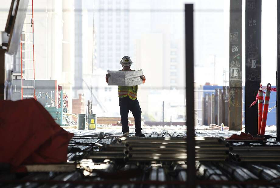A construction worker studies building plans for the California Pacific Medical Center hospital project on Van Ness Avenue in San Francisco, Calif. on Thursday, Aug. 27, 2015. Structural engineers are bolting 119 viscous wall dampers in the exterior walls to minimize or eliminate damage during a major earthquake. Photo: Paul Chinn, The Chronicle