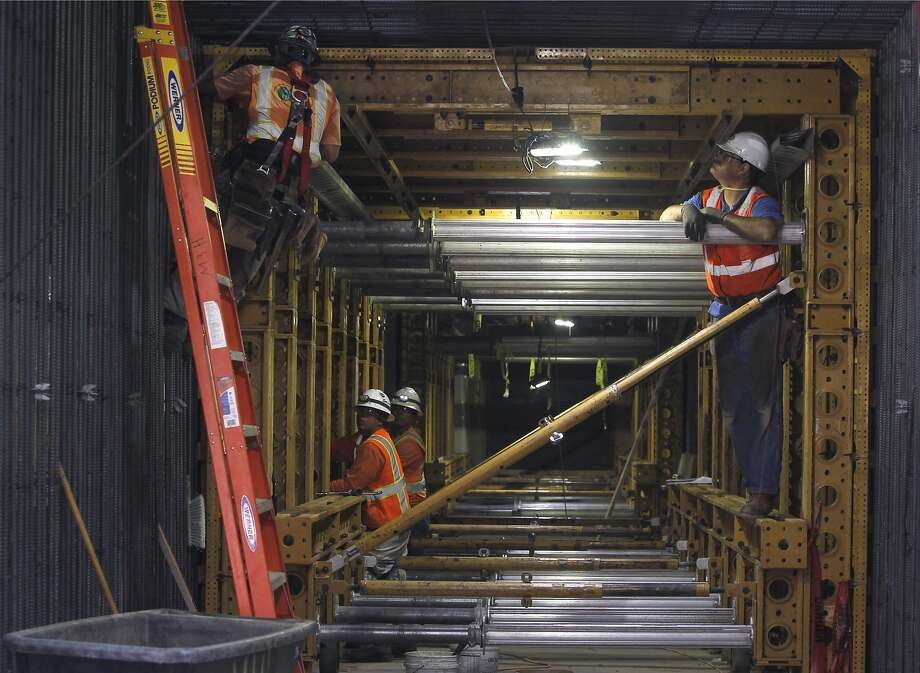 A construction crew works inside the pedestrian tunnel below Van Ness Avenue for the California Pacific Medical Center hospital project in San Francisco, Calif. on Thursday, Aug. 27, 2015. Structural engineers are bolting 119 viscous wall dampers in the exterior walls to minimize or eliminate damage during a major earthquake. Photo: Paul Chinn, The Chronicle