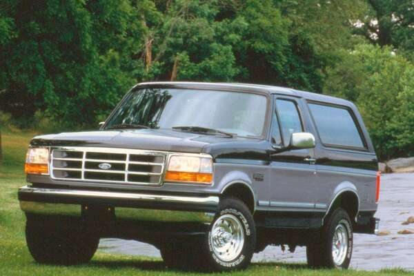 An older model Ford Bronco is shown.