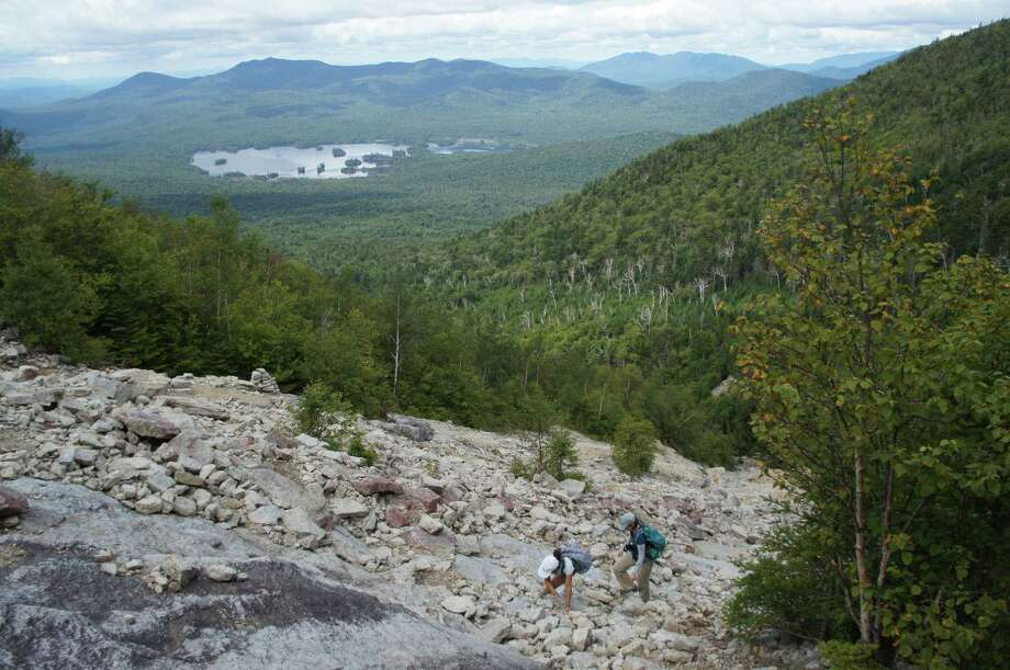 Gillian Scott with rookie hiker Andrea on the slide on Macomb Mountain in the Adirondack High Peaks. (Herb Terns / Times Union)