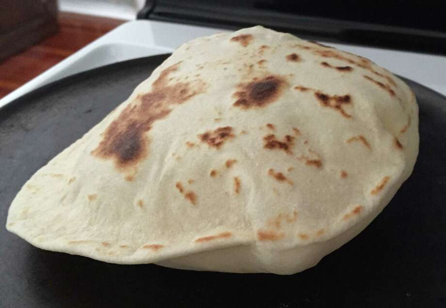 A flour tortilla puffing on a comal. Burn marks indicate the homemade variety. Photo: Edmund Tijerina / San Antonio Express-News
