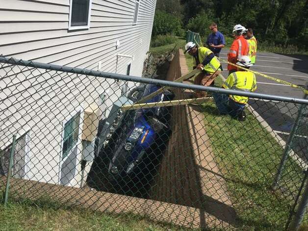 Officials try to decide how to remove an electrical service box from a car that got wedged between this home in North Greenbush and a retaining wall. (Lori Van Buren / Times Union)