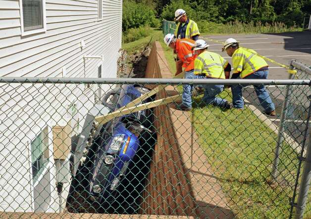 National Grid workers try to pry the electric service panel off a Ford Mustang that fell in-between an apartment building and a retaining wall on Oak Hill Circle on Thursday, Aug. 27, 2015 in North Greenbush, N.Y. A tow truck was waiting to lift the car out. (Lori Van Buren / Times Union) Photo: Lori Van Buren / 0033161A