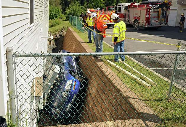 National Grid workers try to figure out how to get the electric service panel off a Ford Mustang that fell in-between an apartment building and a retaining wall on Oak Hill Circle on Thursday, Aug. 27, 2015 in North Greenbush, N.Y. A tow truck was waiting to lift the car out. (Lori Van Buren / Times Union) Photo: Lori Van Buren / 0033161A