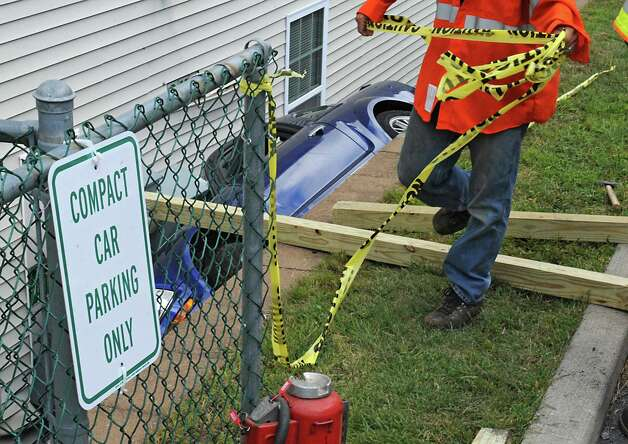 An sign is seen on the fence next to a Ford Mustang that fell in-between an apartment building and a retaining wall on Oak Hill Circle on Thursday, Aug. 27, 2015 in North Greenbush, N.Y. A tow truck was waiting to lift the car out. (Lori Van Buren / Times Union) Photo: Lori Van Buren / 0033161A