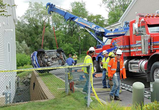 A tow truck lifts a Ford Mustang that fell in-between an apartment building and a retaining wall on Oak Hill Circle on Thursday, Aug. 27, 2015 in North Greenbush, N.Y. (Lori Van Buren / Times Union) Photo: Lori Van Buren / 0033161A