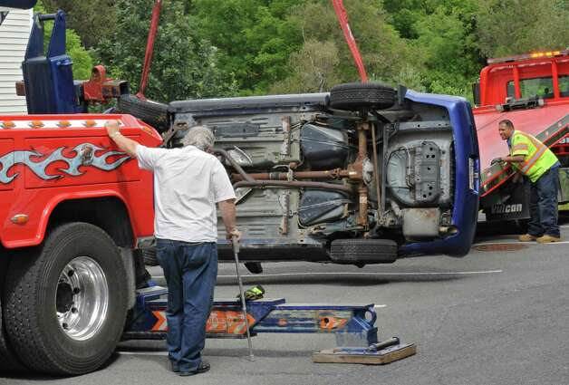 The driver of the Ford Mustang that fell in-between an apartment building and a retaining wall watches his car get prepped to be towed away on Oak Hill Circle on Thursday, Aug. 27, 2015 in North Greenbush, N.Y. (Lori Van Buren / Times Union) Photo: Lori Van Buren / 0033161A