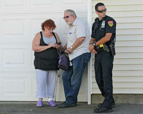 A police officer stands next to the woman and man who were rescued from their Ford Mustang that fell in-between an apartment building and a retaining wall on Oak Hill Circle on Thursday, Aug. 27, 2015 in North Greenbush, N.Y. (Lori Van Buren / Times Union) Photo: Lori Van Buren / 0033161A