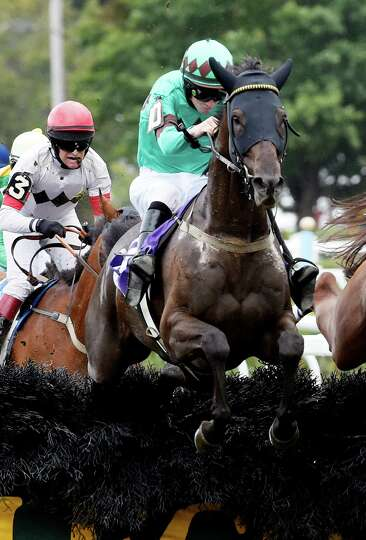 Bob Le Beau with jockey William McCarthy aboard jumps the final fence of the 2 3/8 mile steeplechase